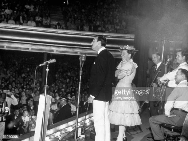 Circa 1965 American actor and singer Jim Nabors performs onstage with American singer and comedian Minnie Pearl at the Grand Ole Opry Nashville...
