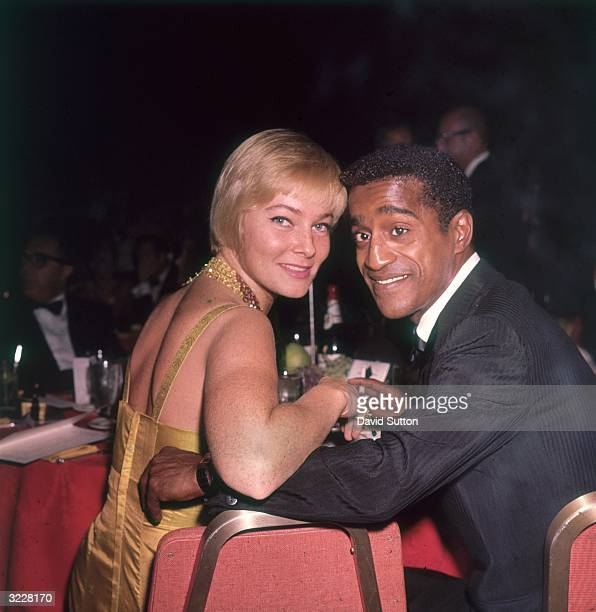 American actor and singer Sammy Davis Jr and his wife Swedish actor May Britt smile over their shoulders while sitting at a table at a formal dinner...