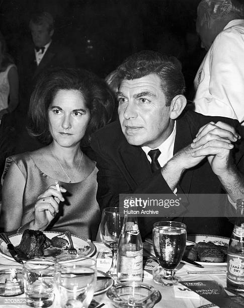 American actor Andy Griffith sits at a restaurant table with his first wife Barbara Edwards She holds a cigarette They have meals on their plates...