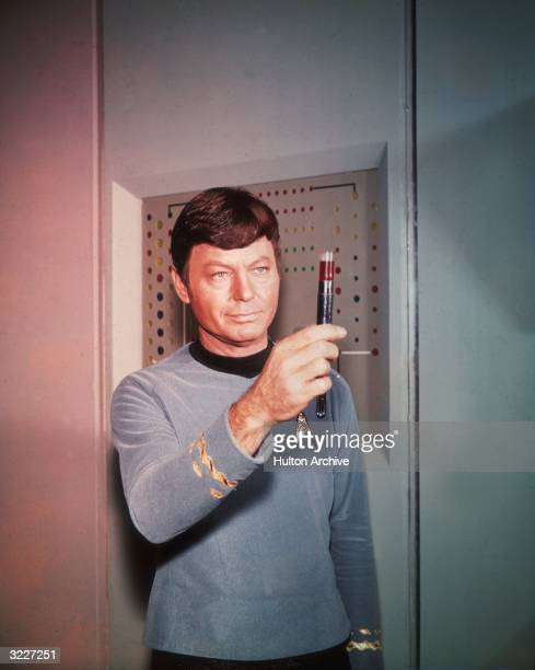 American actor DeForest Kelley portraying Dr 'Bones' McCoy examines a vial filled with a dark substance in a still from the television show 'Star...