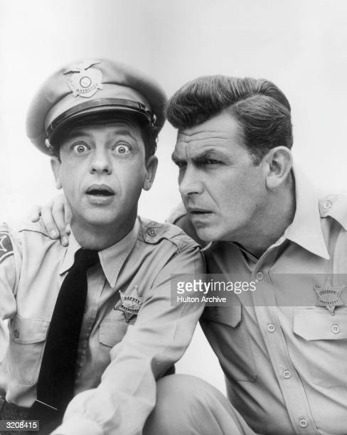 American actor Don Knotts looks at the camera with a surprised expression as Andy Griffith holds his hand on his shoulder posing in character as...