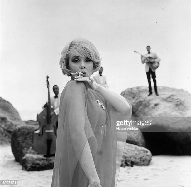 American actor Edie Adams poses on a beach smoking a cigar as two musicians stand in the background with a doublebass and guitar advertising Muriel...