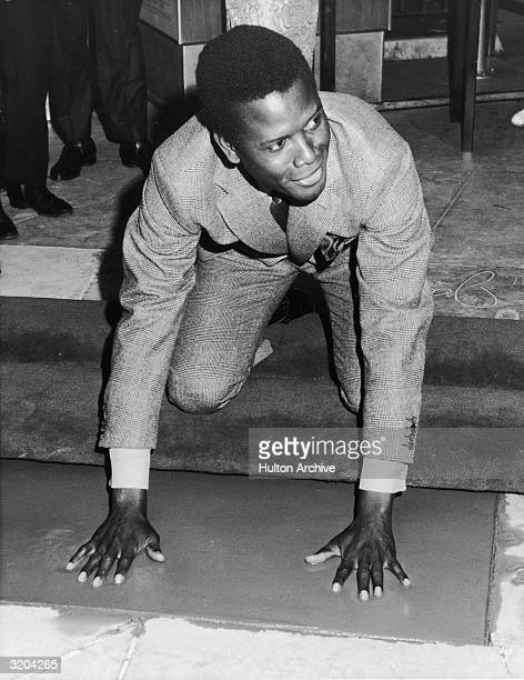 American actor Sidney Poitier kneels to make hand prints in the wet cement at Grauman's Chinese Theatre, Hollywood, California.