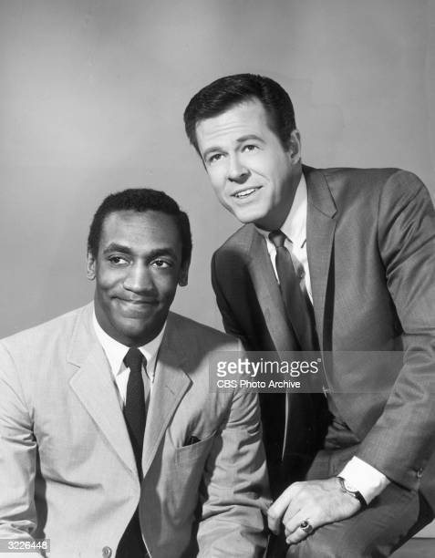 American actors Bill Cosby and Robert Culp pose together in a promotional studio portrait for the television series 'I Spy'