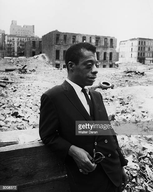 American author James Baldwin leans on a piece of wood standing in the middle of rubble