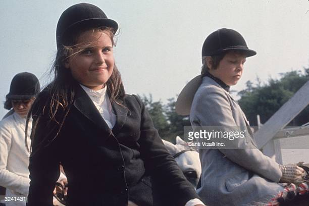 American broadcast journalist Maria Shriver as a young girl riding a horse in Hyannisport, Massachusetts. Behind her are two young boys on horses.