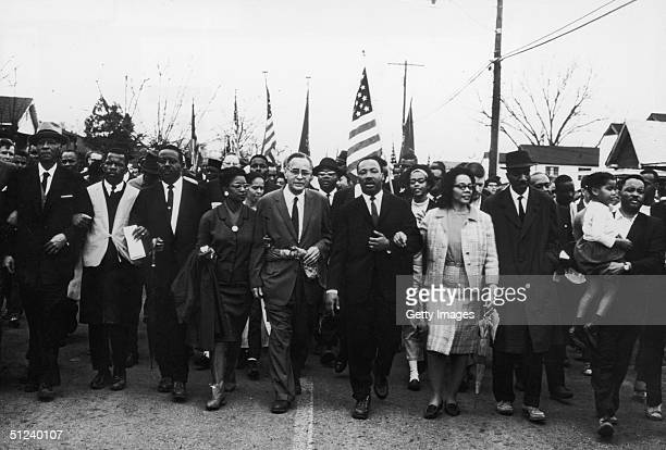 Circa 1965 American civil rights leader Dr Martin Luther King Jr and his wife Coretta Scott King lead a march down the center of a street 1960s