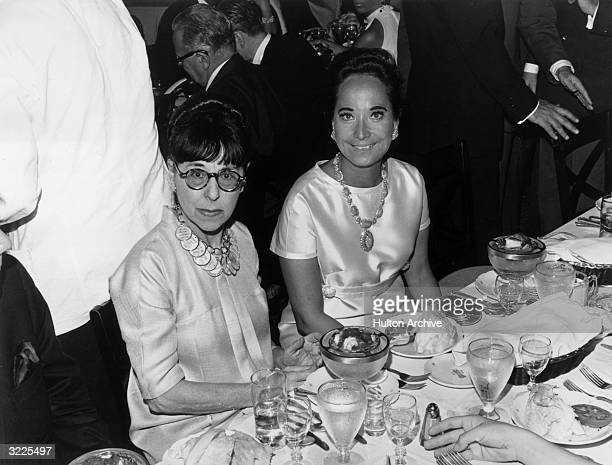 American costume designer Edith Head and Indianborn actor Merle Oberon sitting next to each other at a dining table