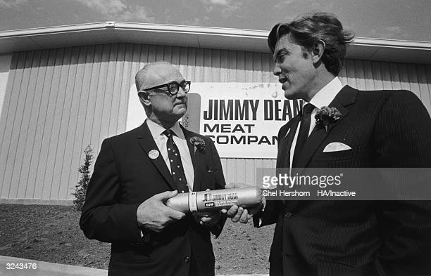 American country singer and business executive Jimmy Dean and an elderly man hold a tube of sausage at the opening of a new Jimmy Dean Meat Company...