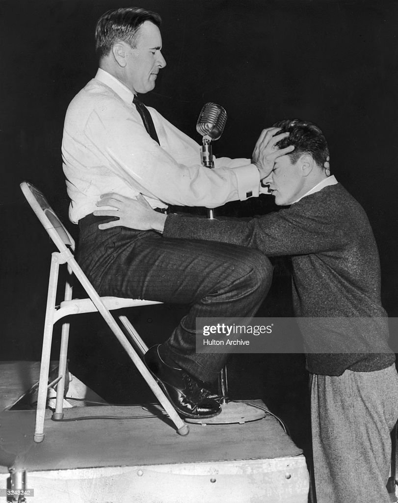 American evangelist Oral Roberts sits on a platform and holds his hand over a man's forehead as the man clutches his waist on stage during a prayer tour. They both have their eyes closed.