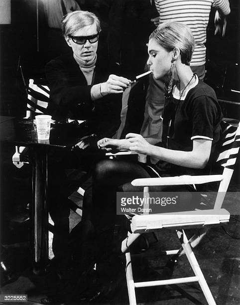 American Pop artist Andy Warhol sits next to actor Edie Sedgwick and lights her cigarette on the set of one of his films