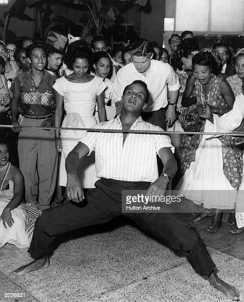 American singer and actor Harry Belafonte maneuvering under a limbo bar in bare feet while a crowd smiles and cheers.
