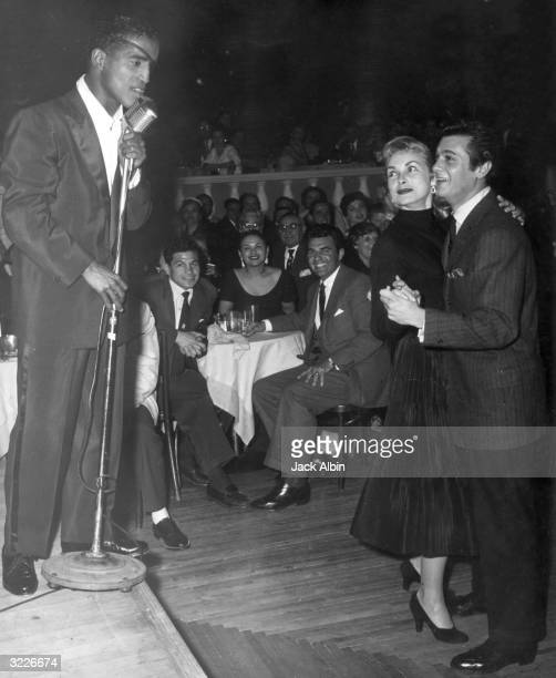 American singer and actor Sammy Davis Jr sings on stage at a microphone as married American actors Janet Leigh and Tony Curtis dance at Ciro's...