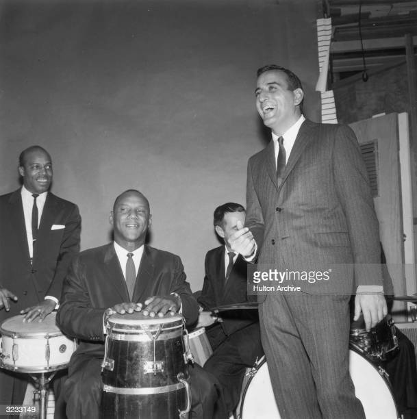 American singer Tony Bennett smiles and snaps his fingers during a performance with a percussion band Bennett is wearing a pinstriped suit and a tie
