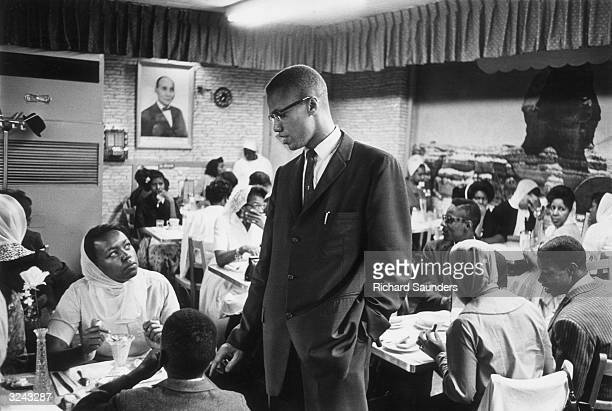 Black nationalist and Muslim leader Malcolm X talking to a woman inside Temple 7 a Halal restaurant patronized by black Muslims and situated on Lenox...