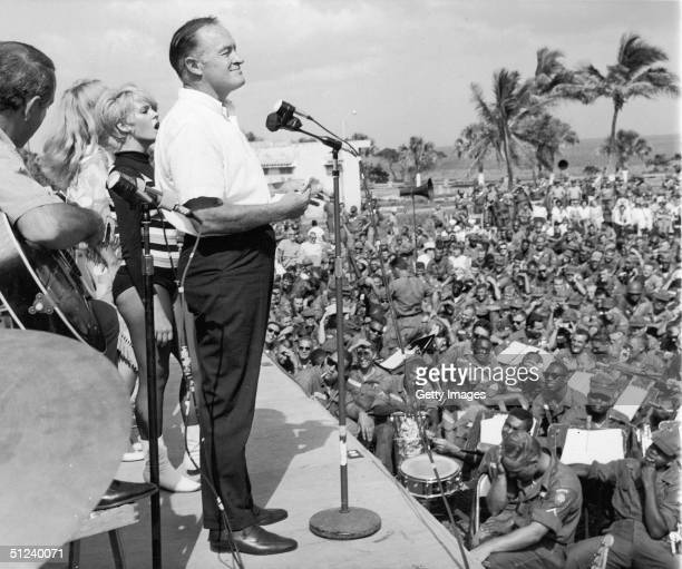 Circa 1965 British born American comedian and actor Bob Hope performs before US troops in front of the Hotel Hispanola which was being used as...