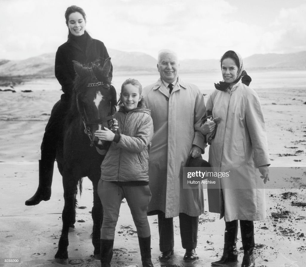 British-born actor and filmmaker Charlie Chaplin (1889 - 1977) stands with his fourth wife Oona (1926 - 1991) (R) and two of his daughters, Geraldine (L, on horse) and Jane, outdoors near a lake, Ireland. Charlie and Oona wear trenchcoats; the girls wear riding attire.