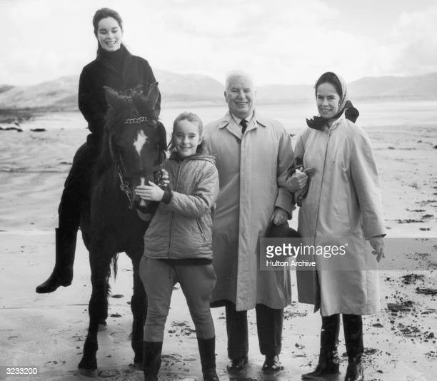 Britishborn actor and filmmaker Charlie Chaplin stands with his fourth wife Oona and two of his daughters Geraldine and Jane outdoors near a lake...