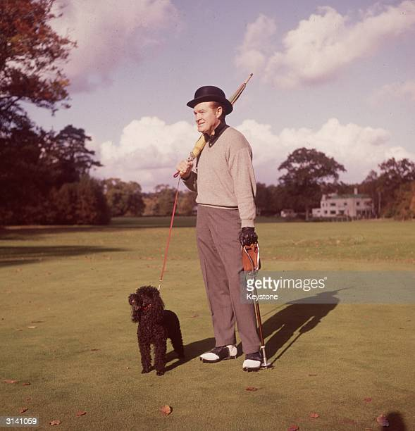 British-born American comedian and actor Bob Hope out walking on an English golf course with an umbrella, a shooting stick and a black poodle.