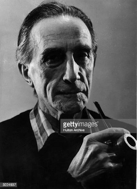 Closeup of French Dada artist Marcel Duchamp holding a pipe.