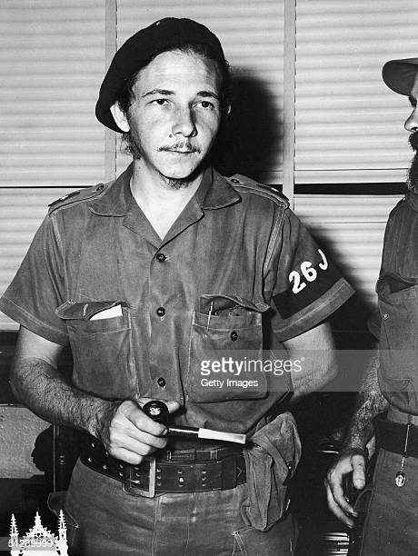 Circa 1965 Cuban revolutionary Fidel Castro's younger brother Raoul Castro stands holding a pipe and wearing his uniform inside his headquarters in...