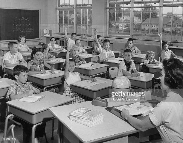Elementary school students raise their hands to answer their teacher's question in a classroom.