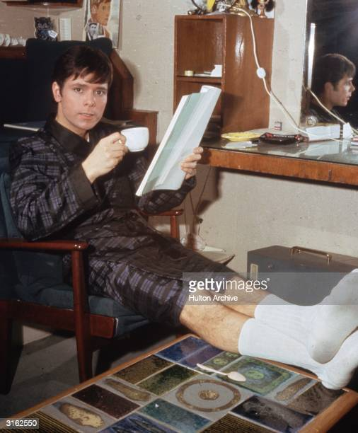English pop star and teen idol Cliff Richard relaxing at home with a cup of tea