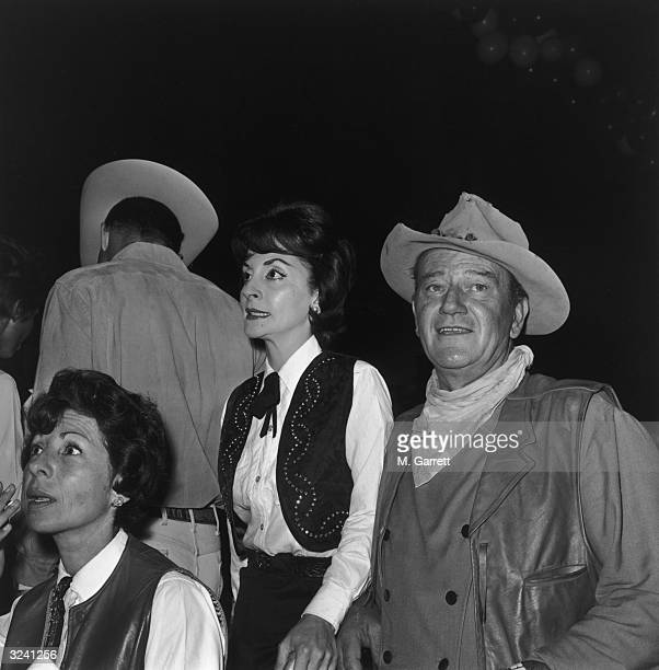 EXCLUSIVE American actor John Wayne and his wife Pilar wear Western costumes at a SHARE Boomtown party Moulin Rouge nightclub Hollywood California
