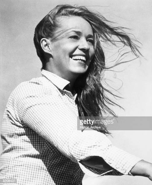 French actor Jeanne Moreau smiles as her hair blows in the wind