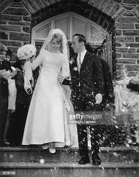 Fulllength image of a man and woman walking out of a chapel after their wedding as the crowd showers them with confetti The bride holds a bouquet