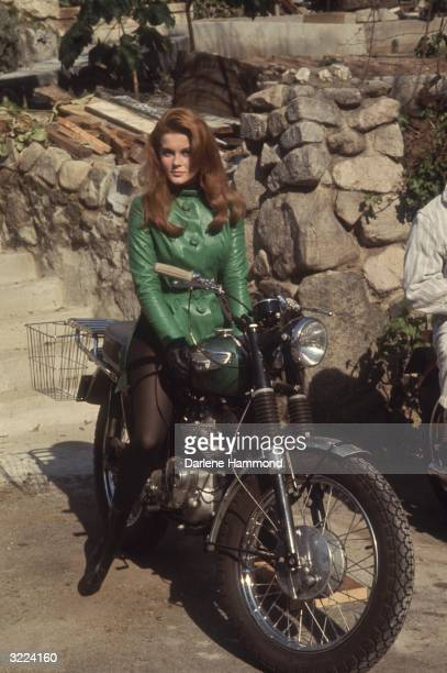 Fulllength portrait of Swedishborn actor and singer AnnMargret wearing a green leather jacket and black tights sitting on a motorcycle outdoors