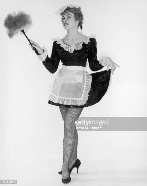 Fulllength studio portrait of a French maid holding a feather duster and lifting her skirts