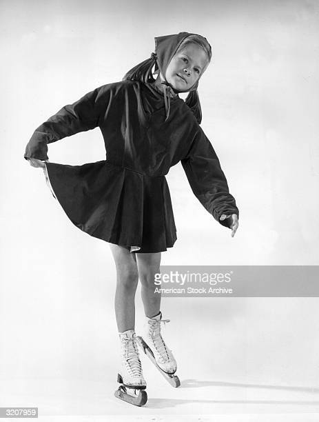 Fulllength studio portrait of a girl wearing a handkerchief on her head posing on ice skates