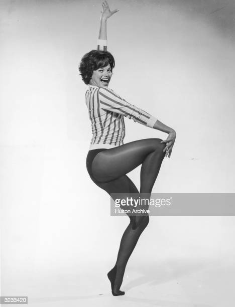 Fulllength studio portrait of Indianborn dancer and actor Juliet Prowse dancing in dark tights and a striped shirt