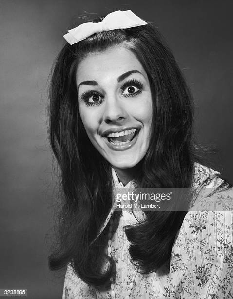 Headshot of a woman with straight dark hair smiling widely with a bow in her hair She wears a patterned blouse