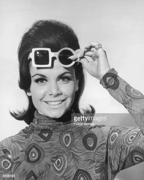 Headshot portrait of American actor and singer Annette Funicello lifting up her sunglasses and smiling 1960s She wears a blouse with peacock plume...