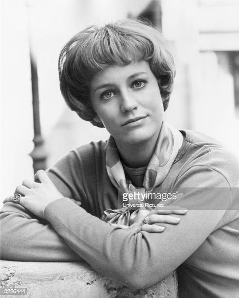 Headshot portrait of American actor Carrie Snodgress crossing her arms She is wearing a crewneck sweater and scarf tied around her neck