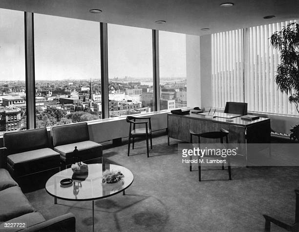 Interior view of an executive office with a wooden desk reception seats and large picture windows overlooking a town There are vertical blinds behind...