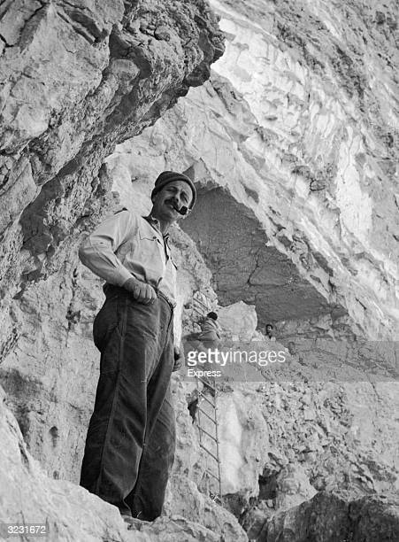Israeli archaeologist and military leader Yigael Yadin smokes a pipe in front of the 'Cave of Letters' where the Dead Sea Scrolls were discovered in...