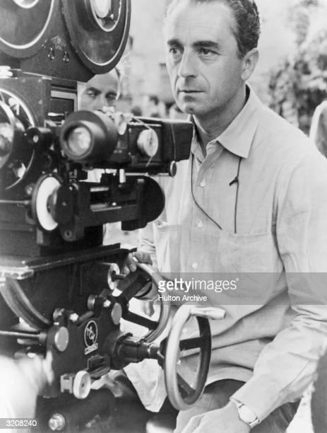 Italian film director Michelangelo Antonioni sits behind a movie camera on a film set