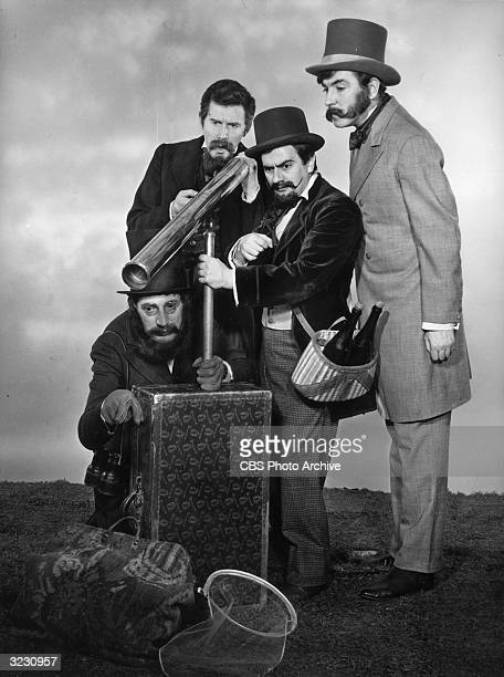 Left to right British comedic actors Jonathan Miller Alan Bennett Dudley Moore and Peter Cook stand around a telescope in a promotional portrait for...