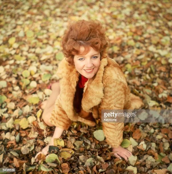 Liverpudlian pop singer Cilla Black sits amidst the autumn leaves
