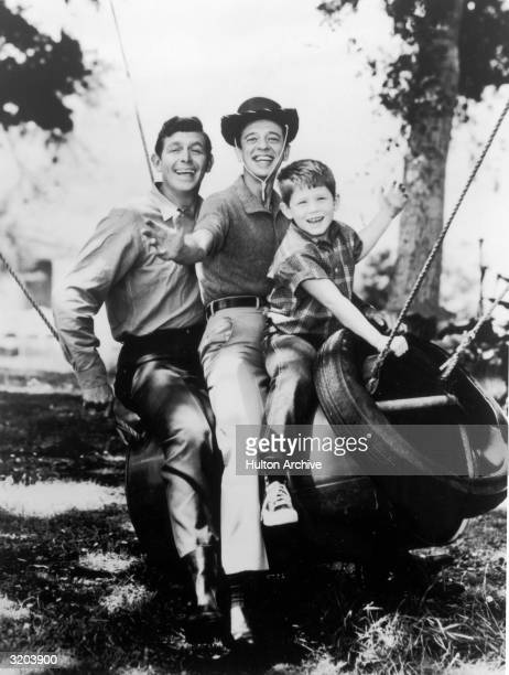 LR American actors Andy Griffith Don Knotts and Ron Howard sit on a metal swing smiling in a promotional portrait for the television series 'The Andy...
