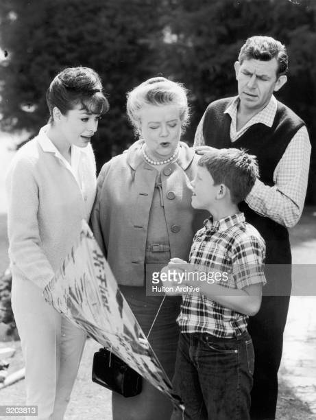 LR American actors Aneta Corseaut Frances Bavier Ron Howard and Andy Griffith talk outdoors in a promotional still for the television series 'The...