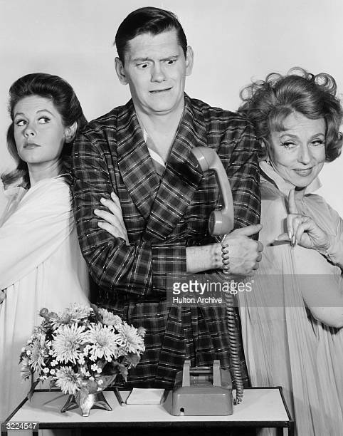 American actors Elizabeth Montgomery, Dick York, and Agnes Moorehead, all wearing sleepwear, looking at a telephone with a levitating receiver, in a...