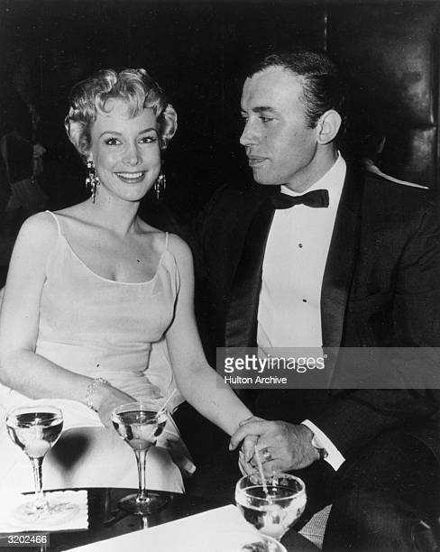 Married American actors Barbara Eden and Michael Ansara holding hands while seated at a table with cocktails in formal attire