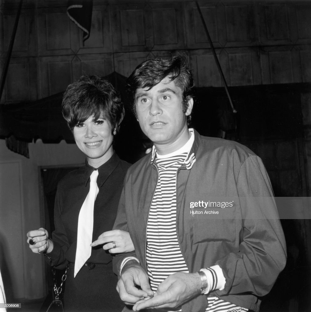 Married American actors James Farentino and Michele Lee walking arm-in-arm at the Daisy Club. Lee has Beatles haircut and wears a dark shirt with a white tie.