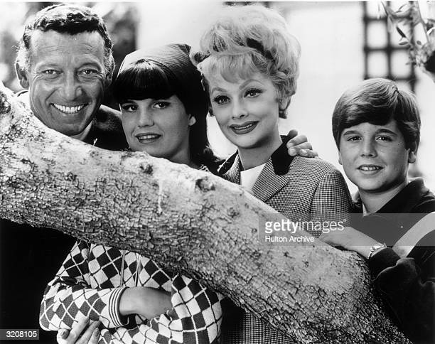 Outdoor portrait of American comedic actor Lucille Ball posing behind a tree branch with her second husband Gary Morton and her children Lucie Arnaz...