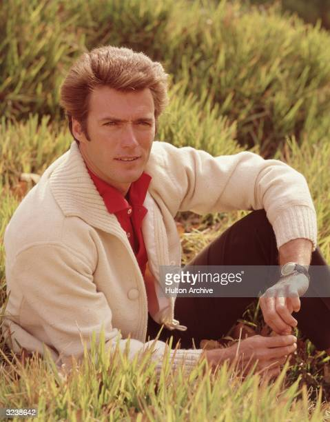 Portrait of American actor and director Clint Eastwood sitting in a field with his leg bent and his elbow resting on his knee 1960s Eastwood is...