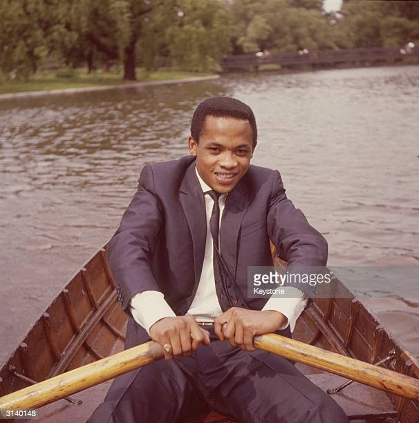 South African singer Danny Williams rows a boat across the lake in London's Regent's Park